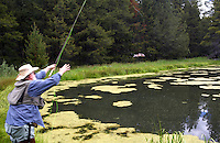 Fly fisherman releasing redband trout on small pond in Freemont National Forest. Oregon