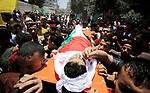 Mourners carry the body of Palestinian Haitham al-Jamal, 15, who was shot dead by Israeli troops during clashes, during his funeral in Rafah in the southern Gaza Strip on June 9, 2018. Four Palestinians were killed by Israeli fire on the Gaza border on June 8, the territory's health ministry said giving a new toll, as weeks of deadly clashes with protesters continued. Photo by Ramadan Elagha