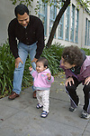 Berkeley CA Adoptive parents (Dad Cuban) of Guatemalan baby, eleven-months-old, proudly observing her new walking skills,