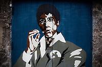 Napoli, Campania, Italia. 23.02.2014. En dør i utkanten av Napoli sentrum er preget av et bilde av Al Pacino som Mafiabossen Tony Montana. Montana fremstår som et forbilde for mange av Camorra lederne, enkelte har til og med laget residenser i tro kopi av hans egen i filmen Scarface. Bilder til magasinsak om Campania regionen.  Foto: Christopher Olssøn
