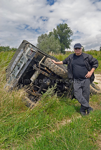 Driver proudly presenting his Land Rover Series 2a Lightweight on its side after it slipped off the track into a ditch while driving off road in Bining, France. --- No releases available. Automotive trademarks are the property of the trademark holder, authorization may be needed for some uses.