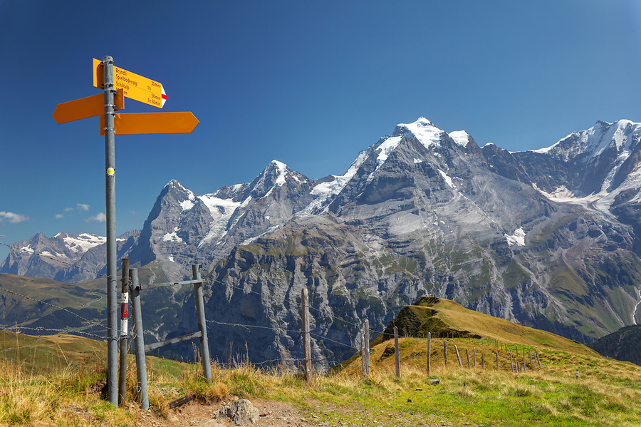Hiking signpost on Wasenegg ridge on Schilthorn mountain, Eiger, Mönch and Jungfrau in background, Switzerland