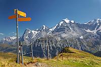 Hiking signpost on Wasenegg ridge on Schilthorn mountain, Eiger, Mönch and Jungfrau in background, Switzerland