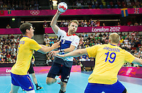 31 JUL 2012 - LONDON, GBR - Ciaran Williams (GBR) of Great Britain (centre, in white, blue and red) shoots during the men's London 2012 Olympic Games Preliminary round match against Sweden at The Copper Box in the Olympic Park, in Stratford, London, Great Britain (PHOTO (C) 2012 NIGEL FARROW)
