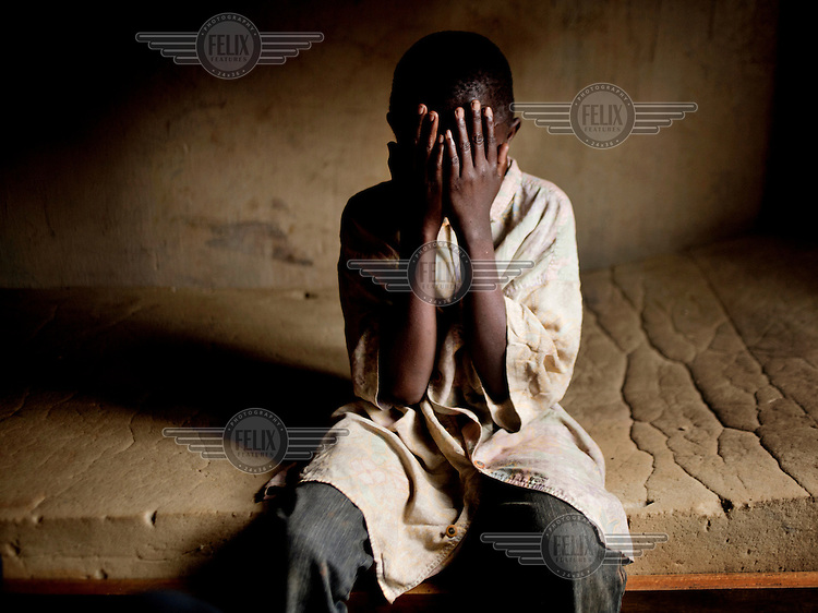 An anonymous boy in his early teens (he is unaware of his own age, but he is approximately 12) is sitting on a bed in a dormitory wearing an oversized shirt. He is a former child soldier. A militia attacked his village and several of his family members were burned alive. After the raid he decided to pick up arms and join another militia to revenge the killings. After serving some time in the militia he was handed over to the Red Cross supported program for former child soldiers.