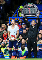 Harry Kane of Spurs smiles and pulls at his shirt and fourth official Graham Scott holds the substitution board during the Premier League match between Chelsea and Tottenham Hotspur at Stamford Bridge, London, England on 1 April 2018. Photo by Andy Rowland.