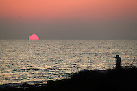 Photographer shooting sunset at Paphos beach,Cyprus.