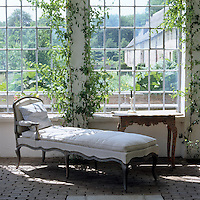 An extended chaise-longue beneath the windows of the orangery