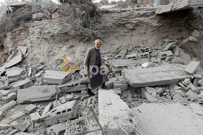 A Palestinian man inspects the rubble of the home of Mohammed Abed Almajid El-Amaira, a Palestinian accused of involvement in a shooting attack that led to the death of a rabbi, after it was destroyed by Israeli military on August 30, 2016 in the West Bank village of Dura near Hebron. Israel frequently destroys the homes of Palestinians who have carried out attacks. Amaira, a member of the Palestinian Authority security services, was arrested several weeks ago, accused of having helped plan and carry out the attack on July 1, when gunmen opened fire on a car near Hebron. The car crashed, killing rabbi Michael Mark, who led a religious school in the Israeli settlement of Otniel, and wounding two family members, according to the army. Photo by Wisam Hashlamoun