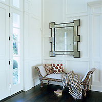 In the entrance hall a large mirror hangs above an antique inlaid daybed beside French windows leading to the garden