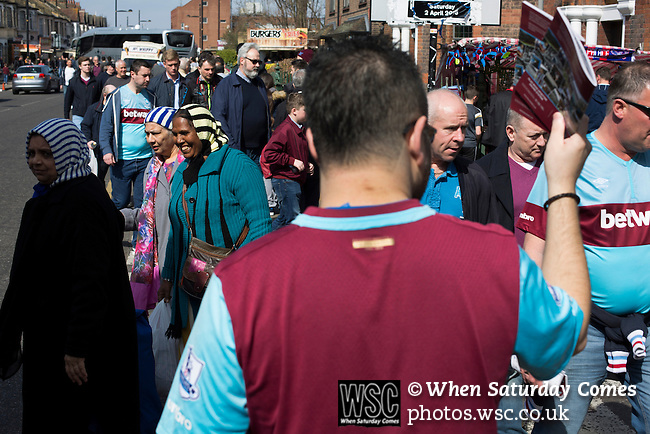 West Ham United 2 Crystal Palace 2, 02/04/2016. Boleyn Ground, Premier League. A fanzine seller tries to attract the attention of fans making their way along Green Street near the Boleyn Ground before West Ham United hosted Crystal Palace in a Barclays Premier League match. The Boleyn Ground at Upton Park was the club's home ground from 1904 until the end of the 2015-16 season when they moved into the Olympic Stadium, built for the 2012 London games, at nearby Stratford. The match ended in a 2-2 draw, watched by a near-capacity crowd of 34,857. Photo by Colin McPherson.