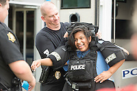 NWA Democrat-Gazette/J.T. WAMPLER Jessenia Anguiano, 14, of Springdale gets help trying on a police vest Tuesday Aug. 4, 2015 from Lt. Leser Coger at Murphy Park during the Springdale Police Department's National Night Out. The event was part of a national campaign to build trust between police officers and city residents. The event featured free food, music, police and fire vehicles on display, contests, a movie and more. The Springdale police department joined more than 16,000 law agencies nationwide to participate in the campaign.<br />