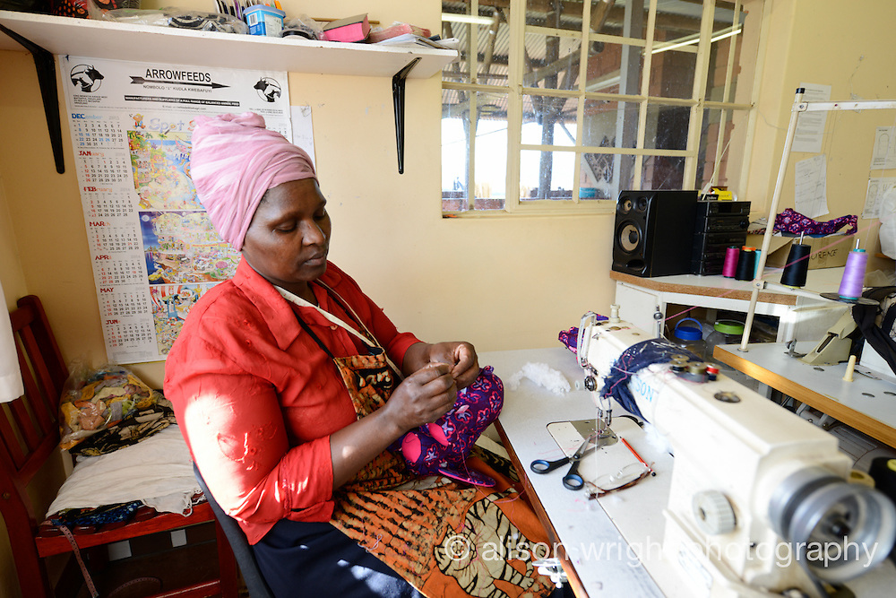 Africa, Malkerns, Swaziland, Nest organization artisans project. Nest is partnering with Baobab Batik & local artisans to help market their batik products to global markets and better sustain their local community. Khanyisile Fakudze (46) sewing at Baobab Batik. She's been a seamstress for 12 years. Has 5 children, 4 grandchildren and this helps with their school fees.