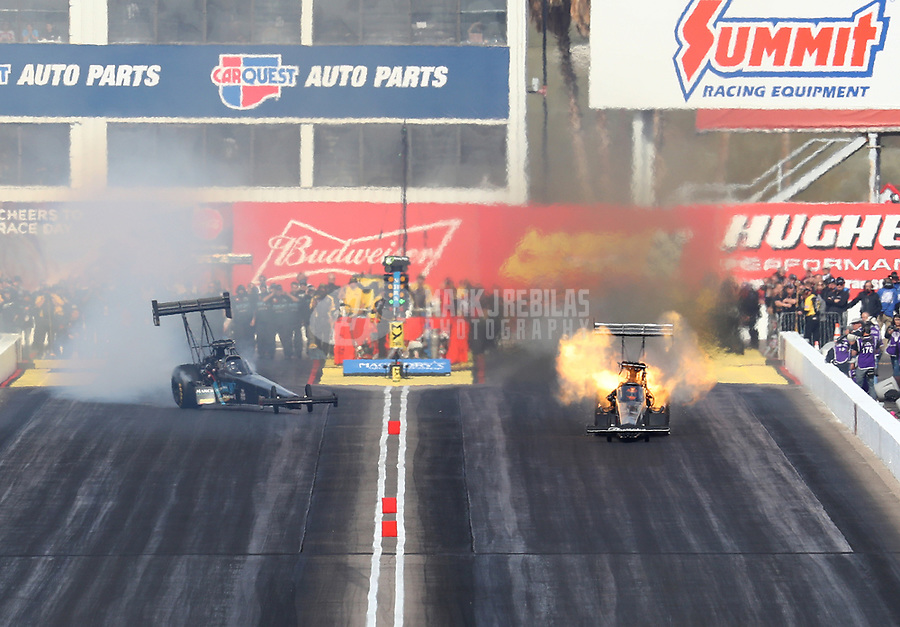 Feb 24, 2019; Chandler, AZ, USA; NHRA top fuel driver Scott Palmer (left) smokes the tires and goes sideways as Mike Salinas explodes an engine during the Arizona Nationals at Wild Horse Pass Motorsports Park. Mandatory Credit: Mark J. Rebilas-USA TODAY Sports
