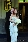 Bride and groom caress prior to their ceremony on a New York City sidewalk  outside the Essex House. y..