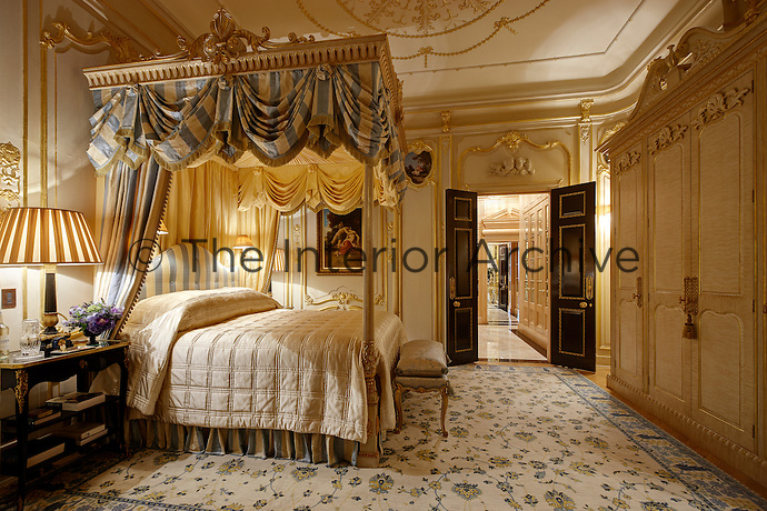 An opulent bedroom with a four poster bed with an ornate gilt top. The room is decorated in blue and white. A free-standing wardrobe stands against one wall.
