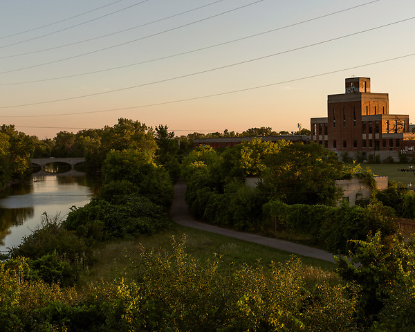 August 5, 2016. Flint, Michigan.<br />  Sunset on the Flint River. The old Flint Water Plant, right, sits on the same lot as the new one. <br />  In April 2014, the city of Flint switched its water source from the Detroit Water and Sewerage Department to using the Flint River in an effort to save money. When the switch occurred, the city failed to have corrosion control treatment in place for the new water. This brought about a leaching of lead from pipes into the water, increasing the lead content in the drinking water to levels far above legal limits. After independent sources brought this to light, the city admitted the water was unsafe and legal battles have ensued between resident and the local and state governments.
