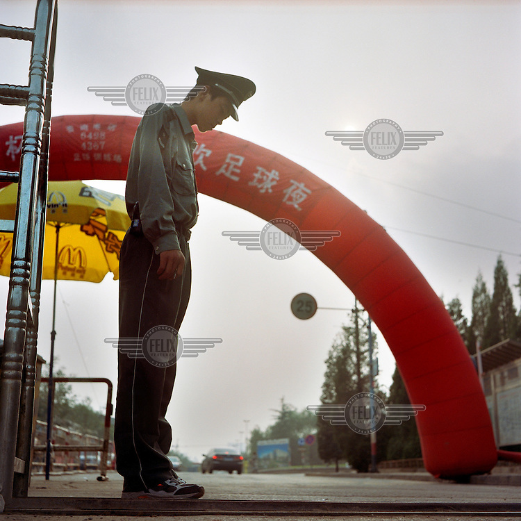A uniformed security guard patrols the entrance to the stadium that will host the 2008 Olympic Games.
