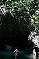 cave tubing guide floats down Caves Branch River into entrance of cave at Jaguar Paw Jungle Resort, Cayo District, Belize, Caribbean, Atlantic, Central America, Caribbean, Atlantic