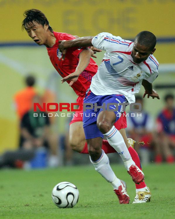 FIFA WM 2006 -  Gruppe D  Vorrunde ( Group D )<br /> Play   #29 (18-Jun) - Frankreich - Korea<br /> <br /> Florent Malouda (rechts) von Frankreich im Zweikampf mit <br /> Young Chul Kim (links) von Korea.<br /> <br /> Foto &copy; nordphoto
