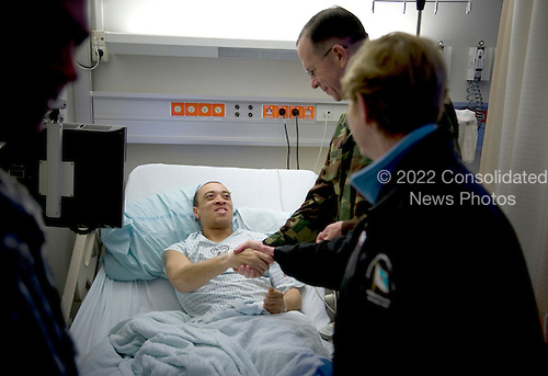 Landstuhl, Germany - December 16, 2008 -- United States Navy Admiral Mike Mullen, chairman of the Joint Chiefs of Staff and his wife Deborah visit with U.S. Army Staff Sergeant Andre Miller, a patient at Landstuhl Regional Medical Center during their first stop on the 2008 USO Holiday Tour on Tuesday, December 16, 2008. Mullen was joined by comedians John Bowman, Kathleen Madigan and Lewis Black; actress Tichina Arnold; American Idol contestant and country musician Kellie Pickler and Grammy award winning musician Kid Rock on the tour bringing joy to service members and their families stationed overseas. .Credit: Chad J. McNeeley - DoD via CNP