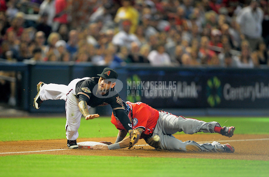 Jun. 4, 2011; Phoenix, AZ, USA; Washington Nationals base runner Ian Desmond is safe at third ahead of the ball to Arizona Diamondbacks third baseman Ryan Roberts in the first inning at Chase Field. Mandatory Credit: Mark J. Rebilas-