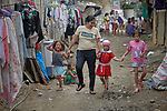Christian Love Daroy-Gagno, the program director of the Kapatiran-Kaunlaran Foundation (KKFI), walks with children in Pulilan, a village in Bulacan, Philippines, where KKFI has an educational program.<br /> <br /> KKFI is supported by United Methodist Women.