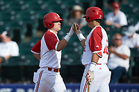Brett Kinneman (left) bumps fists with teammate Evan Mendoza (right) after hitting a home run against the Boston College Eagles in Game Two of the 2017 ACC Baseball Championship at Louisville Slugger Field on May 23, 2017 in Louisville, Kentucky. The Wolfpack defeated the Eagles 6-1. (Brian Westerholt/Four Seam Images)