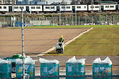 A worker rolls newly laid turf in an athletes' warm-up area of the London 2012 Olympic Park, Stratford.