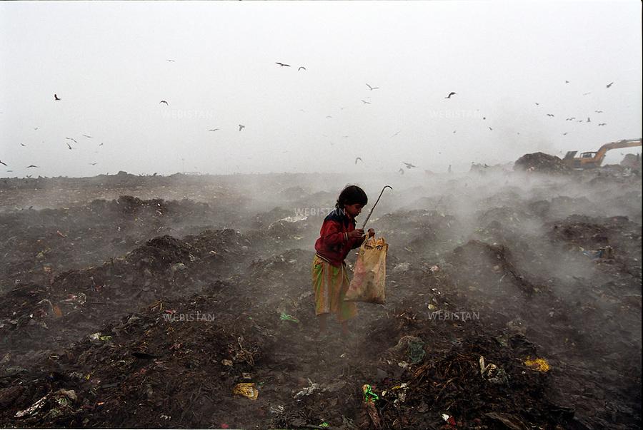 2004..In the cold winter morning, Jasmine collects garbage at the Kajla dumpyard of Dhaka...Dans la décharge de Kajla à Dacca, par un matin froid, Jasmine collecte des ordures.