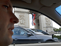 "France. Paris. Arc de Triomphe. Toni Srdanovic drives his car on the Place Charles de Gaulle. Policemen and french flag. The Place Charles de Gaulle, historically known as the Place de l'Étoile, is a large road junction and the meeting point of twelve straight avenues (hence its historic name, which translates as ""Square of the Star""). It was renamed in 1970 following the death of General and President Charles de Gaulle. It is still often referred to by its original name. Model released. 18.06.10 © 2010  Didier Ruef.."