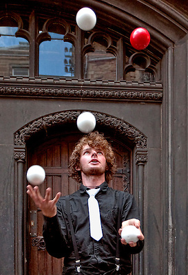 As one of the street entertainers along the Royal Mile during the Festival that includes the Edinburgh Military Tattoo, a young man juggles five balls for tips.