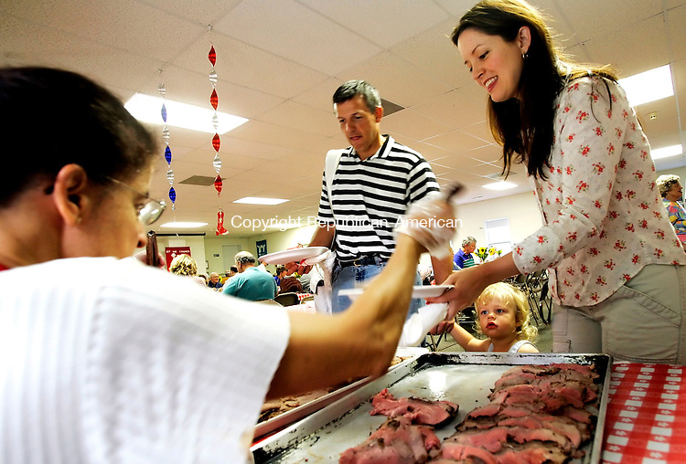 ROXBURY, CT - 13 AUGUST 2005 -081305JS06-- Bill Maier of Roxbury, left, along with his wife Sally and 18-month-old son Will, are served roast beef by church volunteer Jacquie Winterkorn, left, during the annual Roxbury Congregational Church beef barbecue on Saturday. The event is usually held outside but due to Saturday's high temprature and humidity, the event was held indoors.   --Jim Shannon Photo--Jacob Sharr; Colleen Weeks, Mike Grady, Thomaston are CQ
