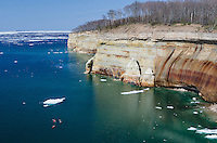 The beautiful Pictured Rocks shoreline and a still icy Lake Superior over Memorial Weekend 2014. A few kayakers can be seen paddling the shore. Munising, MI