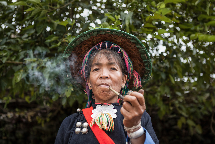 "Portrait of an Wa women smokes pipe in Wengding. The Wa, which literally means ""mountain dwellers"", is the hilltribe that inhabit the Sino-Burmese. Known as one of the last headhunting tribe until mid-twentieth century, their population in both countries now approximately no more than one million. In the homogenous society of modern China, Wa is one of more than 50 officially state-recognized ethnic minorities. They can be found around the southwestern corners of Yunnan province."