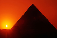 Egypt. Cairo. Giza. Sunset behind The Sphinx and Chephren Pyramid.<br />