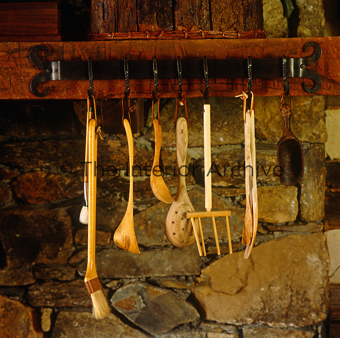Above the stove in this Virginian country kitchen rustic wooden kitchen utensils hang from from a wrought iron bar