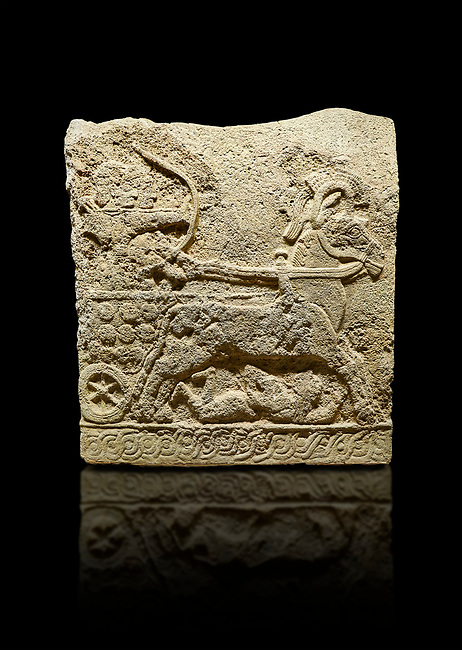 Hittite relief sculpted orthostat stone panel of Long Wall Basalt, Karkamıs, (Kargamıs), Carchemish (Karkemish), 900 - 700 BC. Anatolian Civilizations Museum, Ankara, Turkey.<br /> <br /> Chariot. One of the two figures in the chariot holds the horse's headstall while the other throws arrows. There is a naked enemy with an arrow in his hip lying face down under the horse's feet. It is thought that this figure is depicted smaller than the other figures since it is an enemy soldier. The tower part of the orthostat is decorated with braiding motifs.<br /> <br /> On a black background.