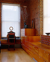 In a New York dressing room the built-in cupboards have been designed in different heights to add to their versatility and the warm wood used in their construction complements the exposed brick of the walls behind