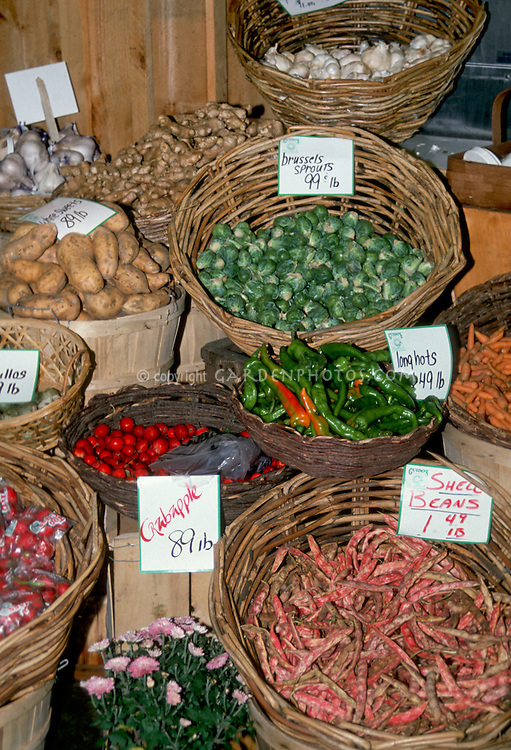 Farm stand for sale vegetables in baskets, brussel sprouts, crabapple malus, shell beans, potatoes, garlic, with prices, carnation flowers . Crab apple