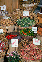 Farm stand for sale vegetables in baskets, brussel sprouts, crabapple malus, shell beans, potatoes, garlic, with prices, carnation flowers