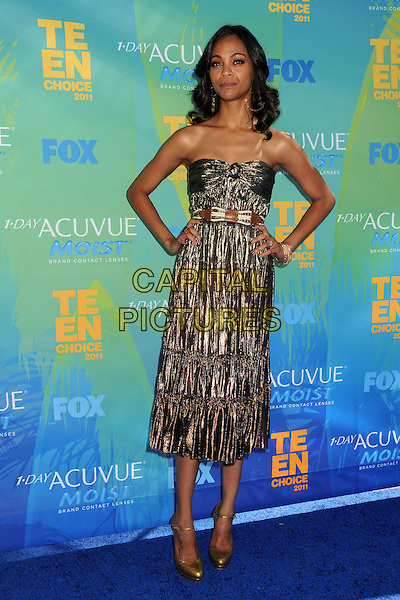 Zoe Saldana.2011 Teen Choice Awards - Arrivals held at Gibson Amphitheatre, Universal City, California, USA..August 7th, 2011.full length strapless gold knot knotted strapless dress silver bronze metallic hands on hips.CAP/ADM/BP .©Byron Purvis/AdMedia/Capital Pictures.
