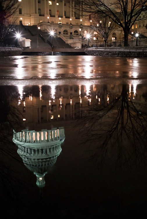 WASHINGTON, DC - March 02: The dome of the U.S. Capitol is reflected on a rain-soaked step on the West Front. The Capitol building is in the background. (Photo by Scott J. Ferrell/Congressional Quarterly)