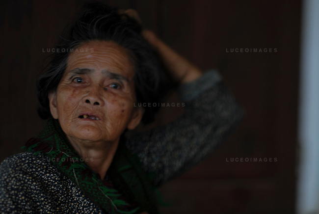 An old woman watch relaxes in the shade of her home in Hoi An, Vietnam.