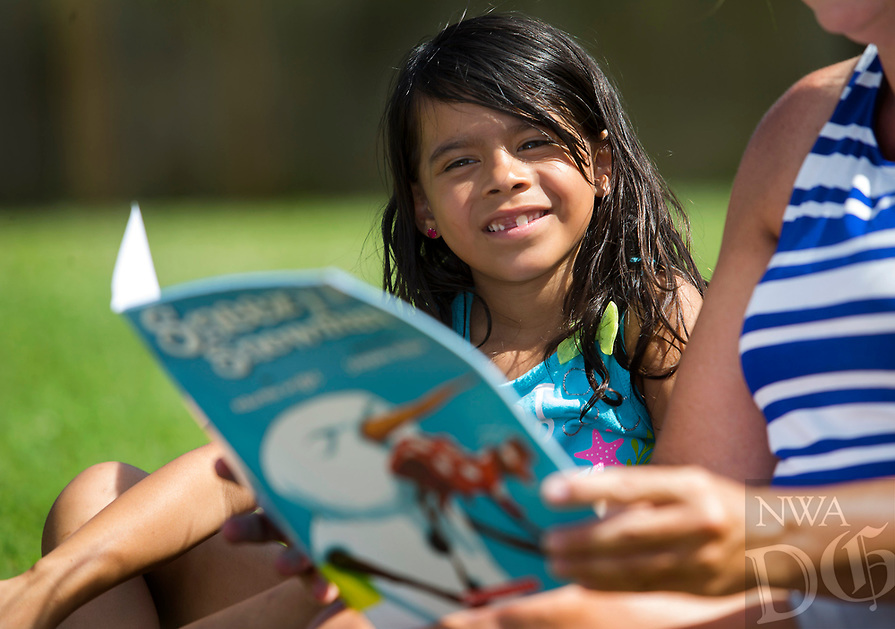 NWA Democrat-Gazette/JASON IVESTER<br /> Breetany (cq) Garcia, 6, listens as Janelle Miller reads Sneezy the Snowman Tuesday, June 13, 2017, at the Montecito Springs Apartment complex in Springdale. The apartments are part of the routine stops for the Sonora Elementary Mobile Library.