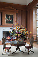 The wood-panelled ante-room adjoining the dining room is filled with the scent of flowers arranged on a small pedestal table