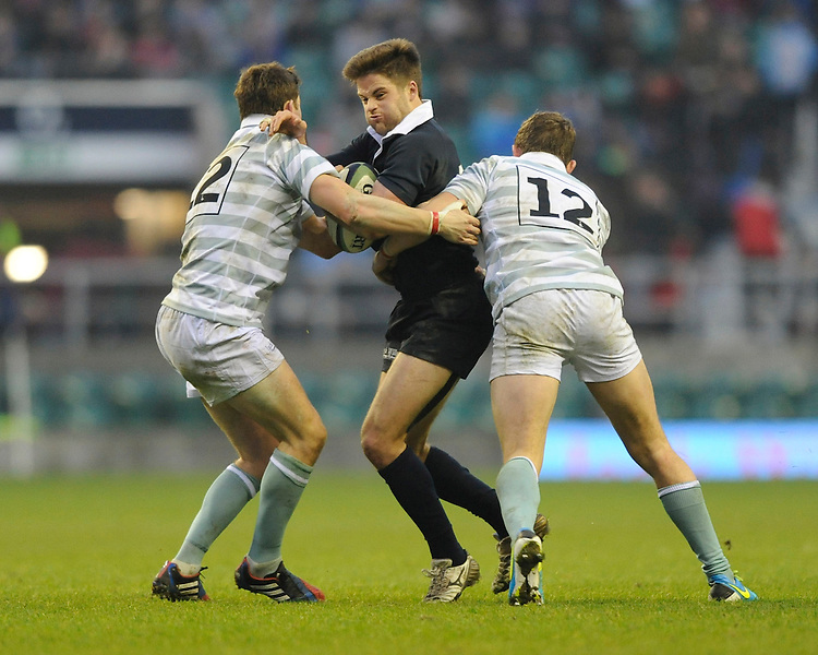 Jacob Taylor of Oxford University is tackled by Andrew Abrahams (left) and Kristian Cooke of Cambridge University during the 132nd Varsity Match between Oxford University and Cambridge University at Twickenham Stadium on Thursday 13th December 2013 (Photo by Rob Munro)