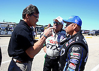 Sept. 21, 2013; Ennis, TX, USA: NHRA funny car driver John Force (center) looks on as Texas governor Rick Perry (left) talks with Robert Hight during qualifying for the Fall Nationals at the Texas Motorplex. Mandatory Credit: Mark J. Rebilas-