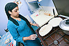 Woman cooking chapati on gas hob in kitchen,