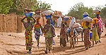 A group of women head home to their villages after a long day at the weekly Friday market in Torodi, Niger.  This morning, they walked many kilometers to Torodi, and now they start the long walk home, carrying their wares on their heads in typical African fashion.